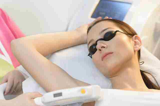 Beautiful woman getting laser hair removal at beauty salon